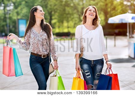 Smiling Young Women With Bags In Shopping