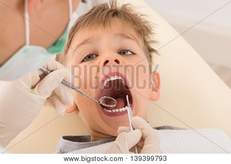 Close-up Of Dentist's Hand Examining Teeth Of Child Patient In Clinic