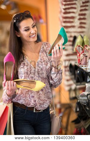 Adult girl chooses summer shoes at store