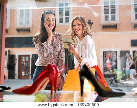 Two beautiful girls window shopping in the city