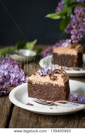 A slice of chocolate mud cake with chocolate frosting