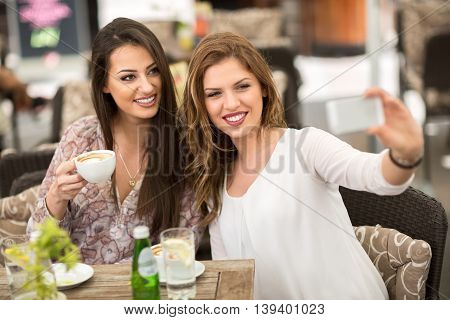 Two smiling female friends driniking coffee and taking selfie friendship concept