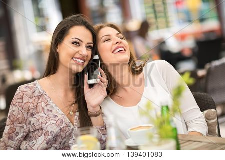 Young female friends laughing while drinking coffee