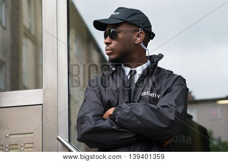 Portrait Of Young African Male Security Guard Standing Arms Crossed
