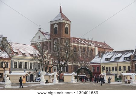 Kaunas, Lithuania - January 3, 2016: Cathedral Basilica of Saint Peter and Saint Paul and town hall square with christmasmas market and statue.