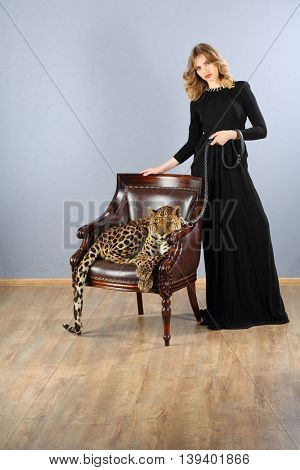 Leopard in chair and pretty woman in dress holding leather leash in studio