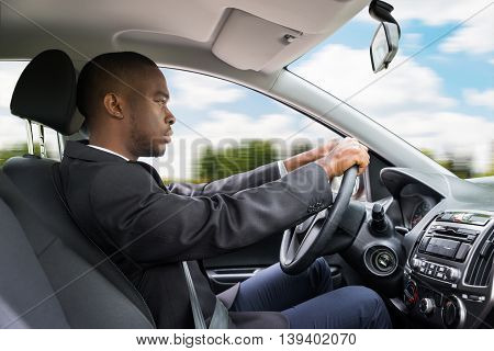 Side View Of A Young Businessman Driving Car