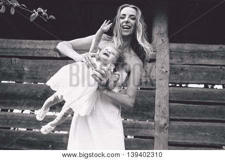 mother playing with his little daughter on the farm