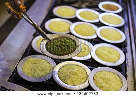 Chef cooking traditional Turkish delicious dessert Kunefe and show cooked Kunefe with pistachio powder closeup