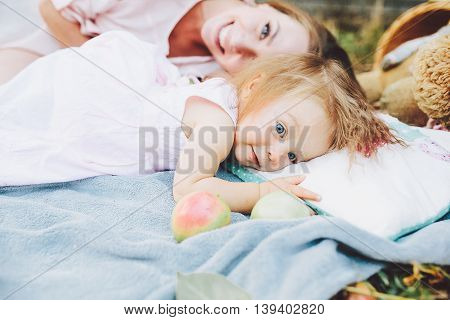 Having fun. Pretty young mother and her little daughter lying on cover in park and having picnic.