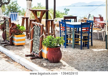 PALEOCHORA, CRETE, GREECE - JULY 2016: Traditional Greek tavern, decorated with  menu on wooden plate.