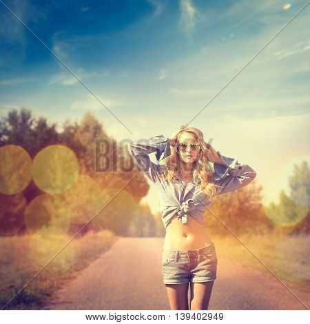 Portrait of Sexy Blonde Woman with Hands behind her Head Walking on Country Road. Toned and Filtered Photo with Bokeh. Hipster Style.