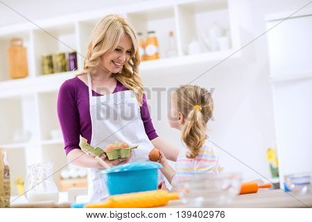 Woman Giving Egg To Daughter