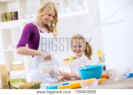 Mother Pouring Milk To Child