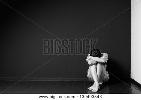 Sad woman sitting in the corner of a room head on the knees face is hidden black and white