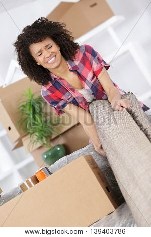 young woman suffering from backache while moving carpet
