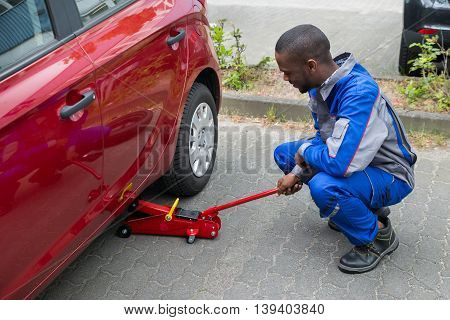 Young Male Mechanic Putting Red Hydraulic Floor Jack Inside The Car