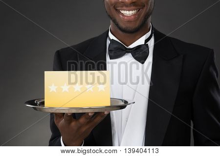 Portrait Of African Waiter Holding Plate With Star Rating