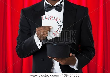 Close-up Of A Male Magician With Playing Cards And Hat