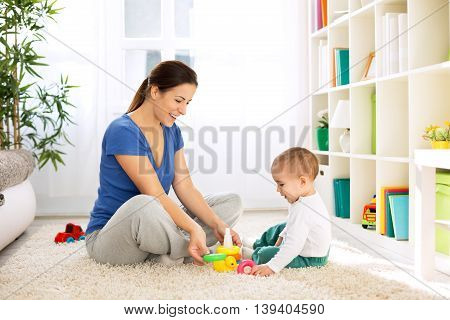 Happy smiling family playing with toys on floor