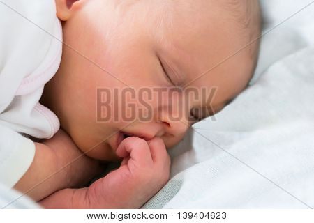 Close-up Of A Little Baby Sleeping With Finger In Her Mouth