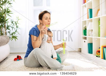Beautiful happy Mother and child blowing bubbles