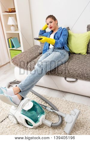Tired Woman Watching Television After Vacuuming