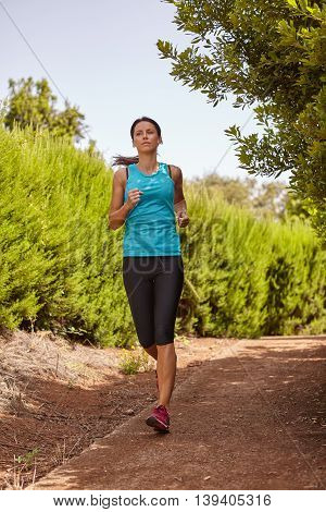 A young female jogger out for a run on a gravel path with bushes behind her wearing casual running clothes in the late morning shadows