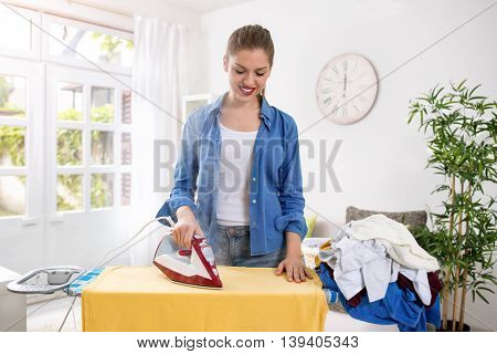 Happy And Smiling Housewife Enjoys In Ironing Her Clothes
