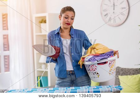 A young beautiful housewife holding iron and basket with clothes