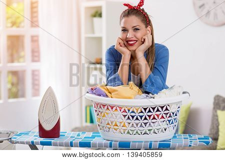 Happy and smiling hostess prepares clothes for ironing at home