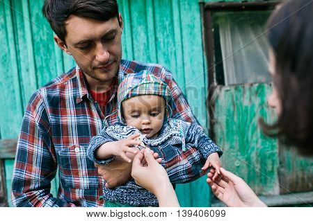 Young family with child posing on the background of an abandoned building