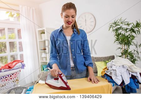 Happy and smiling young housewife enjoys in ironing her clothes