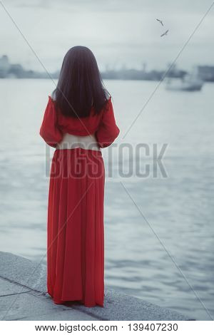 Woman stands on the shore of the sea and waiting.
