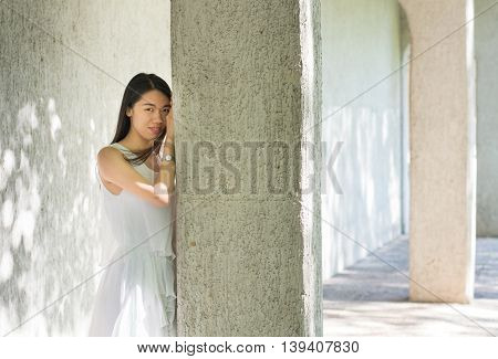 Fashionable Woman Leaning On Stone Pole
