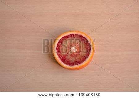 One slice of blood orange on a wooden background