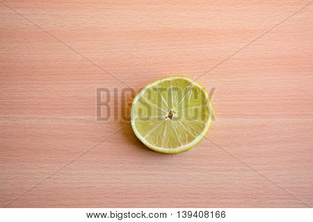 One slice of lime on a wooden background
