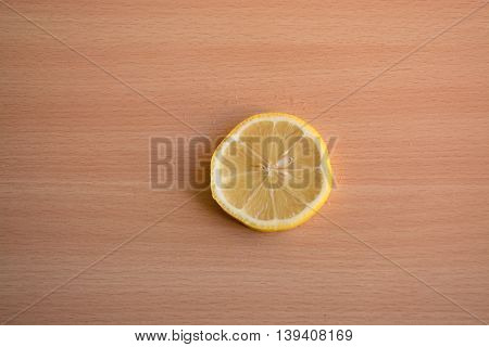 One slice of lemon on a wooden background