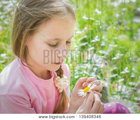 Beautiful thoughtful girl wonders tear off daisy petals while sitting in a meadow