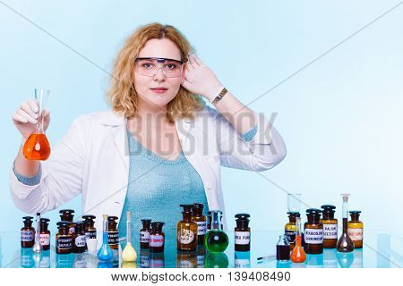 Experiments in laboratory. Chemist woman or student girl scientific researcher with chemical glassware holding hand to ear listening on blue