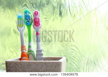 Three Toothbrushes In A Clay Tumbler In The Morning Light Of An Obscured Window