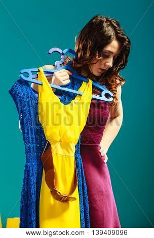 Retail and sale. girl fashionable woman buying clothes. Client customer holding hangers with vivid color clothing blue background