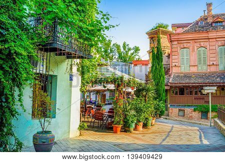 TBILISI GEORGIA - MAY 29 2016: The summer terraces of Shavteli street cafes decorated with numerous plants in pots on May 29 in Tbilisi.
