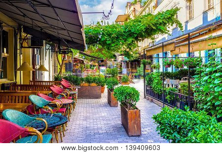 TBILISI GEORGIA - MAY 28 2016: The chairs in summer terrace are turned to the street and the visitors can watch the passers by like in Paris cafes on May 28 in Tbilisi.
