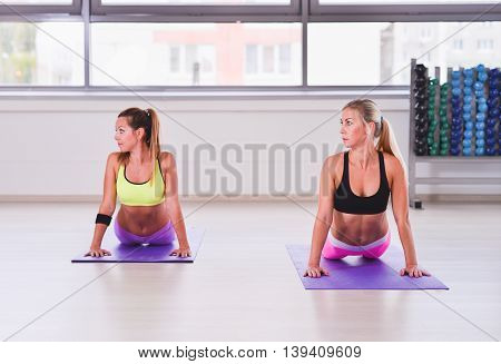 Sporty women practicing yoga cobra pose in fitness class.