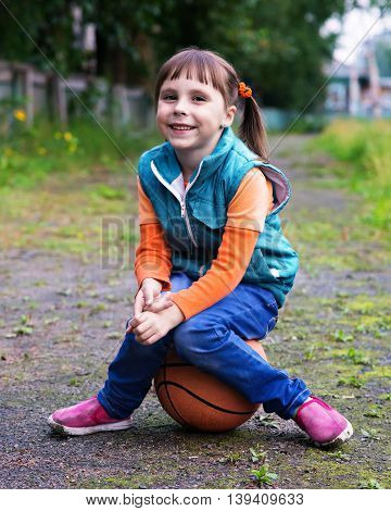 Little girl sitting on a basketball ball in the park and smiling.