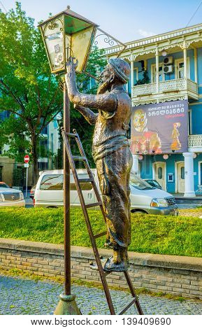 TBILISI GEORGIA - MAY 29 2016: The old lamplighter fixes the streetlight in Baratishvili street of the old town on May 29 in Tbilisi.