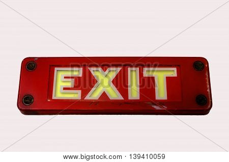 Vintage red metal Exit sign on white wall background with four rusty screws