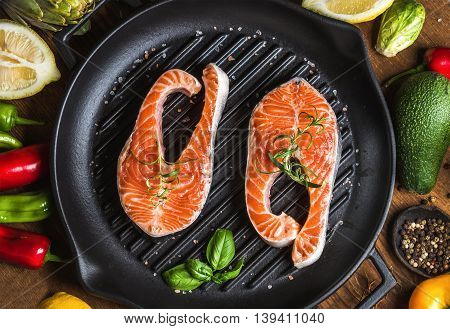 Dinner cooking ingredients. Two pieces of raw uncooked salmon with vegetables, herbs, lemon, avocado, artichokes, spices in iron grilling pan over wooden background, top view, horizontal composition