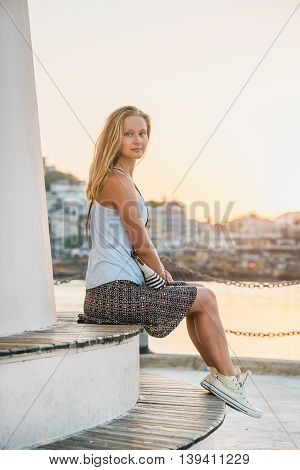 Young blond tourist woman enjoying sunset and sitting on bench of the Lighthouse of Alanya by the sea. Meditarranean region, Turkey.